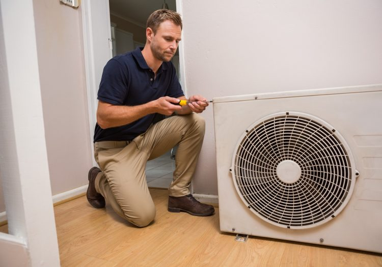 Focused handyman fixing air conditioning in a new house